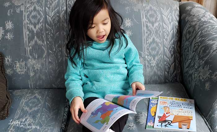 Child reading the Living in Russia book on a sofa