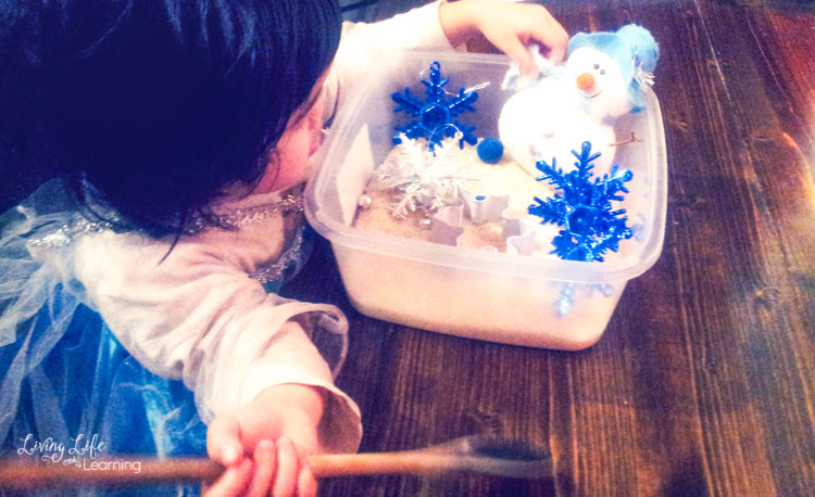 Child playing with snowman sensory bin and wooden spoon.