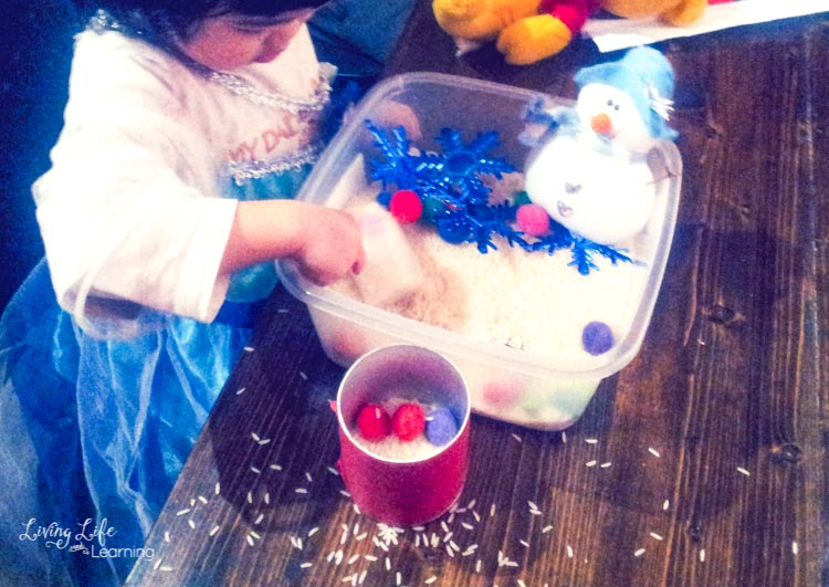 Messy play with rice out of the snowman sensory bin.