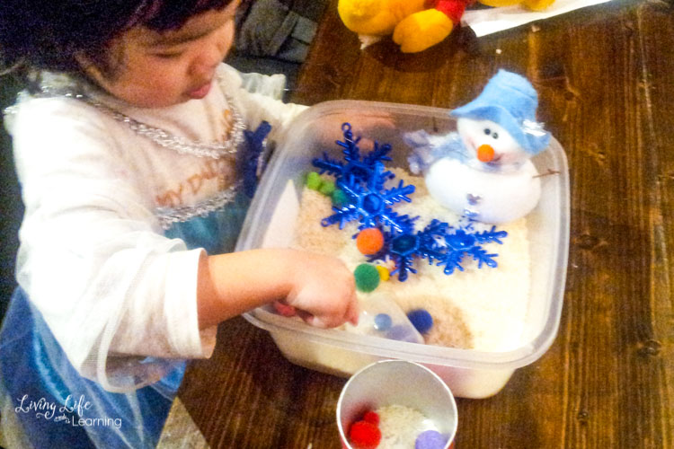 Snowman sensory bin with added pom poms