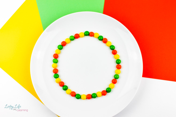A simple skittles experiment set up with yellow green and red skittles in a circle
