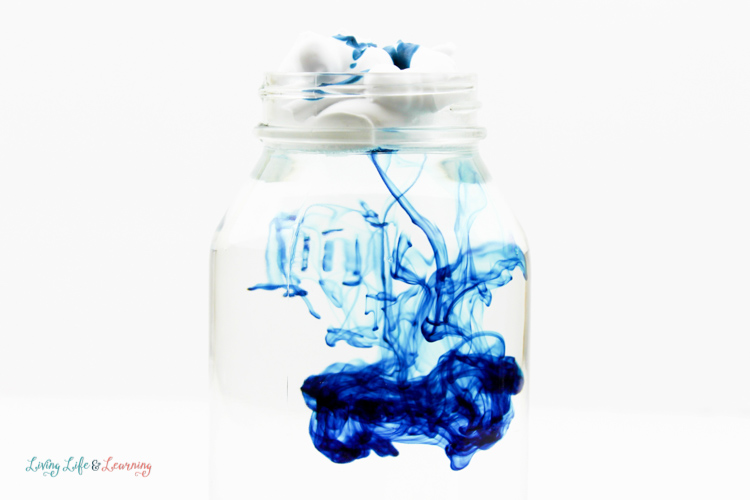 Blue food coloring makes interesting patterns as it drips into a jar in this rain cloud in a jar science experiment.