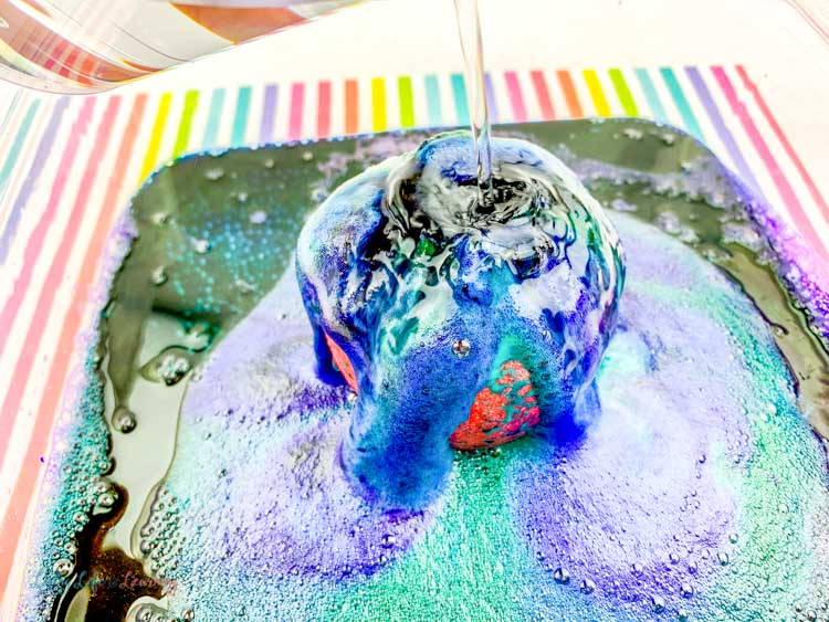 Multicolored ooze from this fizzy fun apple volcano science experiment fills the tray.