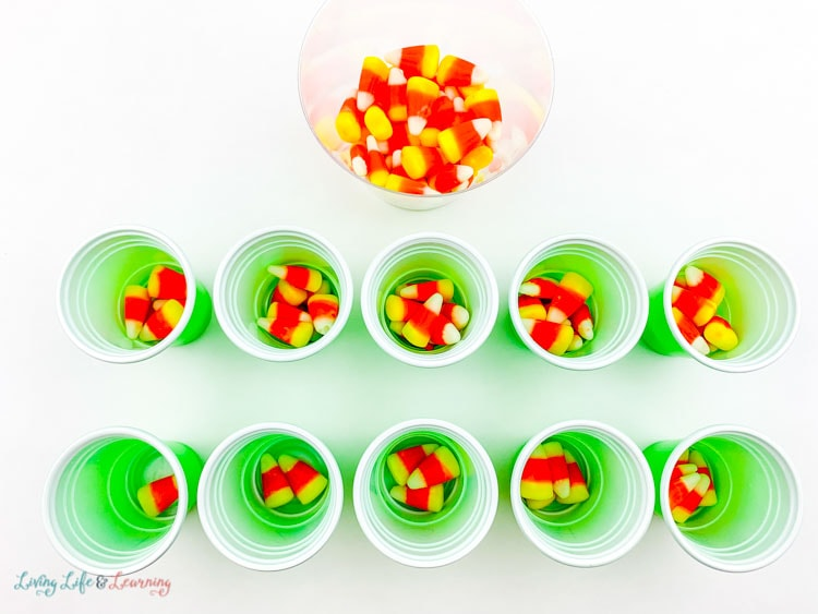Sort the candy corn into the cups according to the number on the cup. Leftover candy is in a bowl beside the cups.