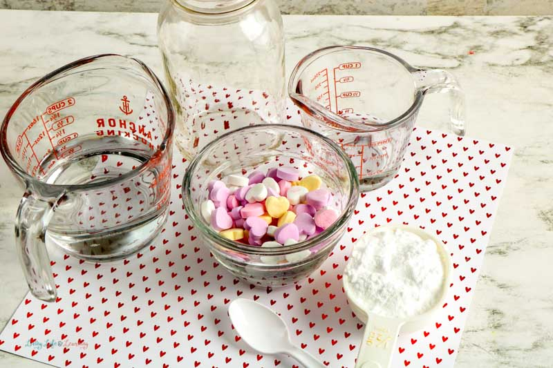 A table with all the supplies needed for the dancing hearts experiment: water, vinegar, baking soda, measuring cup, a jar and candy hearts.