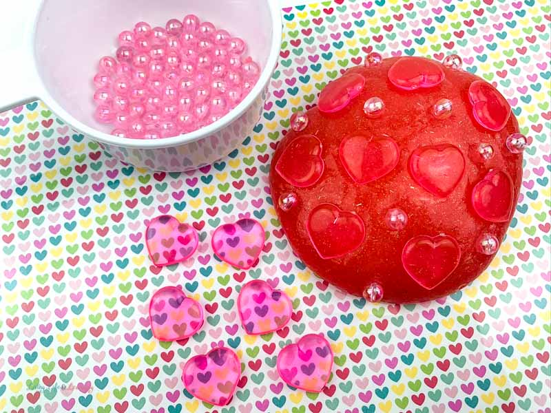 Bowl of gems, small pink hearts, and a ball of red glitter slime with hearts and gems on the table.