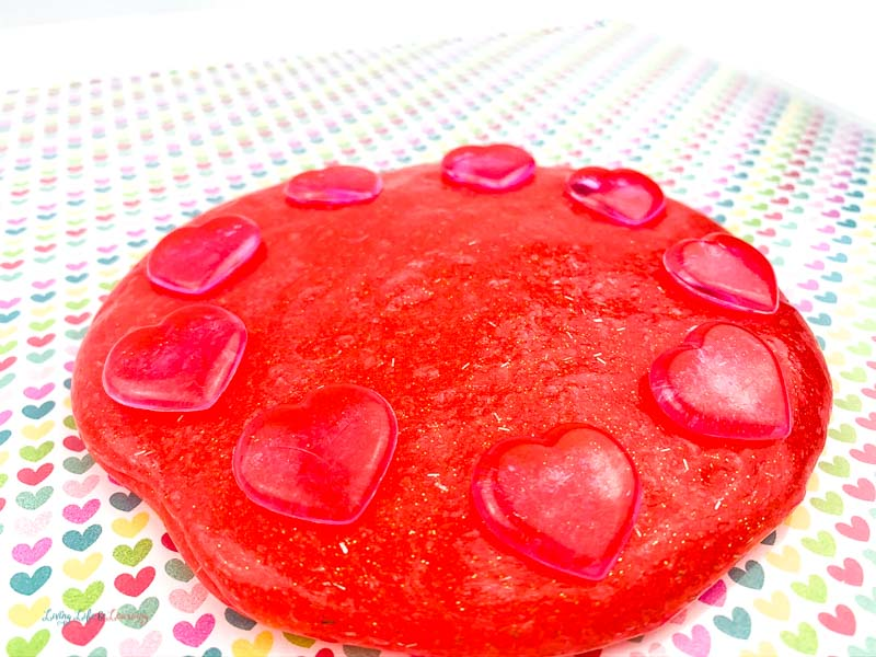 A pile of red glitter slime with hearts and gems on the table.