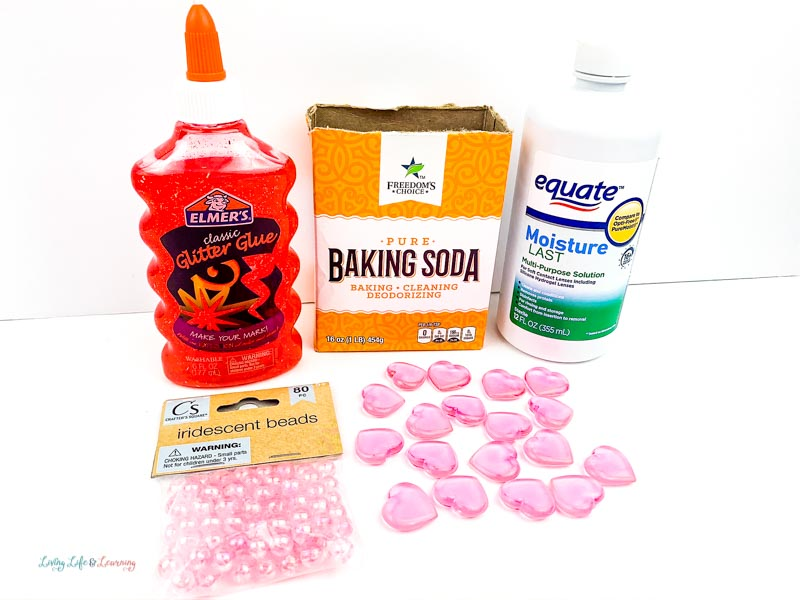 Ingredients needed to make red heart slime: Elmer's glitter glue, baking soda, contact lens solution, small hearts and iridescent beads.