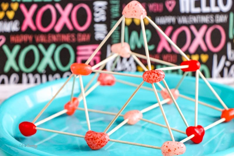 3-D pyramid on a blue plate made by connecting heart-shaped jelly beans and toothpicks.