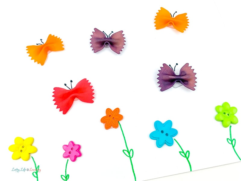 Using a marker to add details to the butterflies and flowers for the Pasta Butterfly Craft